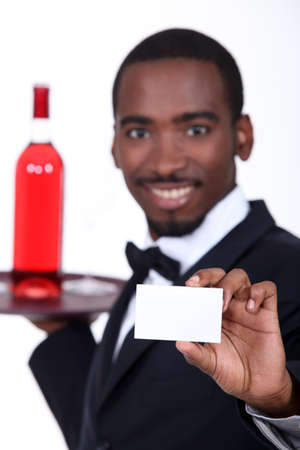 Wine waiter holding forth a business card left blank for your details photo