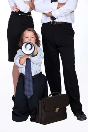 dissension: little boy protesting against business people