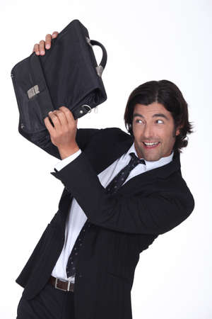 punished: a business man is protecting his face with a briefcase, he looks amused Stock Photo