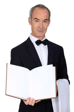 acomodador: Camarero de pelo gris con men� Foto de archivo