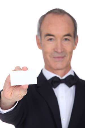 Grey haired waiter displaying business card photo