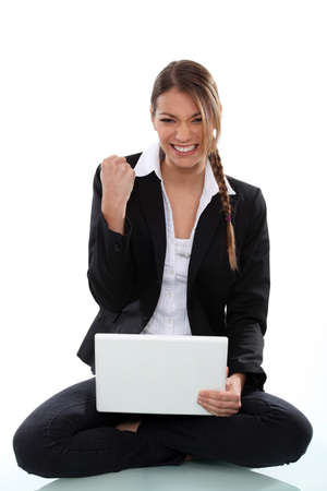 clenching fists: businesswoman with laptop in lotus position clenching her fist