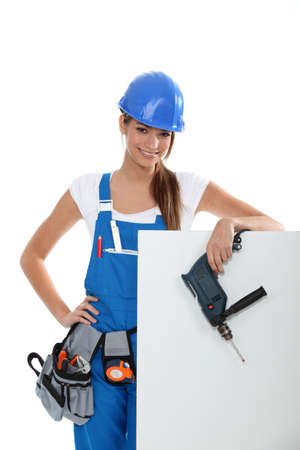 sexy construction worker: Woman with a drill and a blank board Stock Photo