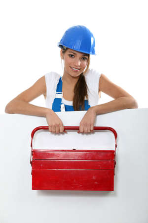 qualified worker: Female labourer with tool box stood behind message board Stock Photo