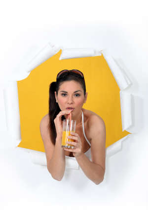 busting: Woman busting through poster drinking orange juice