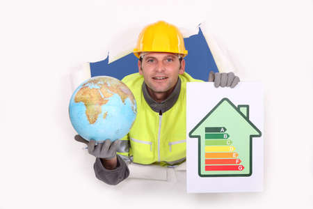 insulation: Tradesman holding a globe and an energy efficiency rating chart
