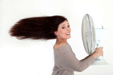 Woman with an electric fan photo
