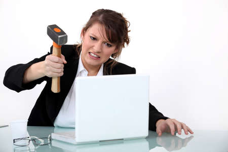 business failure: Woman smashing laptop with hammer