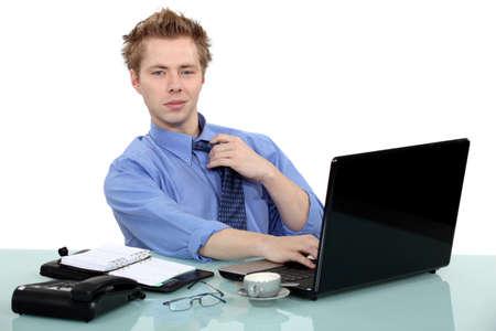 settle back: Man sat at desk