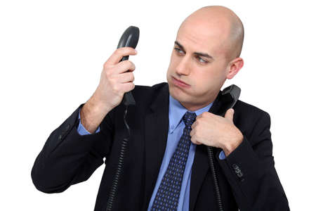 answering phone: Overwhelmed businessman answering telephones Stock Photo