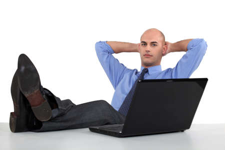 hands behind back: Executive putting his feet up Stock Photo