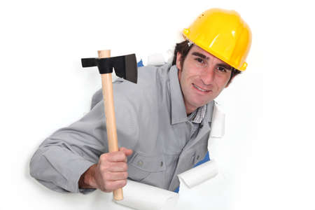 popping out: A man popping out a wall in paper with a hatchet.
