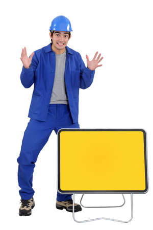 agitated: Agitated worker with a blank road sign Stock Photo