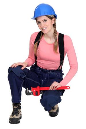 en cuclillas: Mujer electricista holding llave