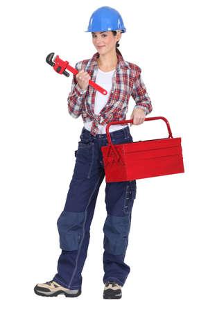 obrero: A tradeswoman la celebración de una llave de tubo y caja de herramientas Foto de archivo