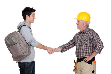 Builder shaking apprentices hand Stock Photo
