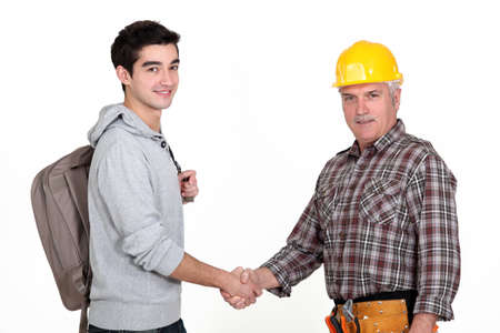 Construction worker shaking hands with a college student