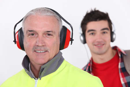 earmuff: Builder with earmuff stood in front of teenager with headphones Stock Photo