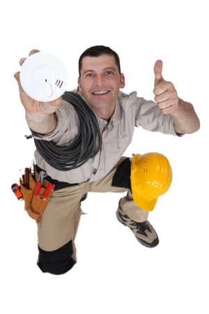 Tradesman holding up a smoke detector Stock Photo - 18944761