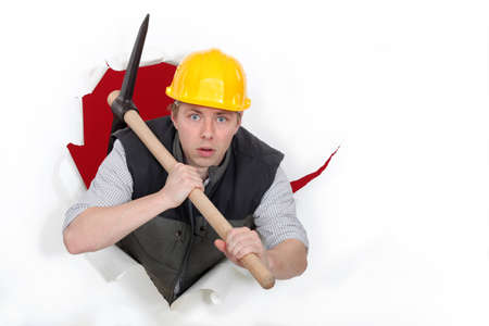 Worker bursting through with a pickaxe Stock Photo - 18947773