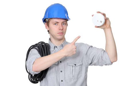 detector: An electrician with a fire detector.