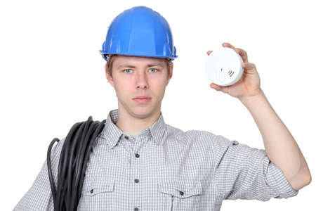 Young electrician holding smoke alarm photo
