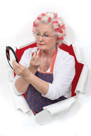 curlers: Senior woman making-up Stock Photo