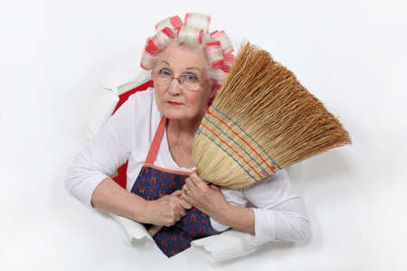 Granny with her hair in rollers holding a broom photo