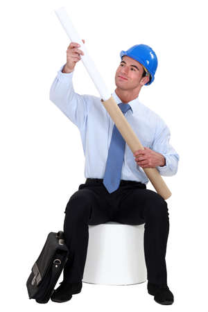 enraptured: Engineer pulling a rolled-up plan out of its case Stock Photo