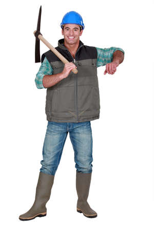 Worker holding pickaxe Stock Photo - 19144542