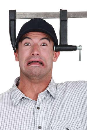 Mann mit seinem Kopf in einem Schraubstock