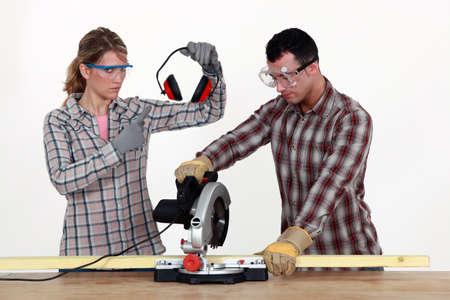 hearing protection: Woman making sure man uses hearing protection Stock Photo