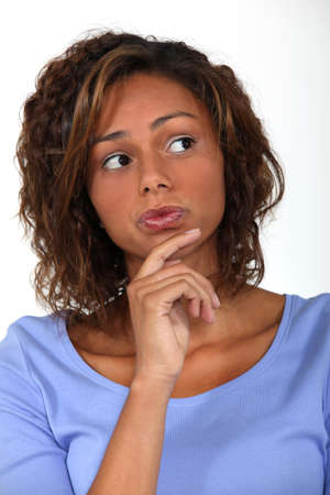 deliberate: woman thinking and holding her chin Stock Photo