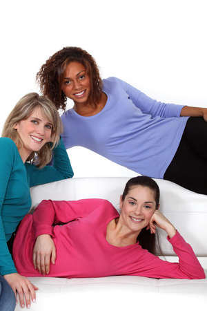 roommates: Portrait of young women sitting on a couch Stock Photo