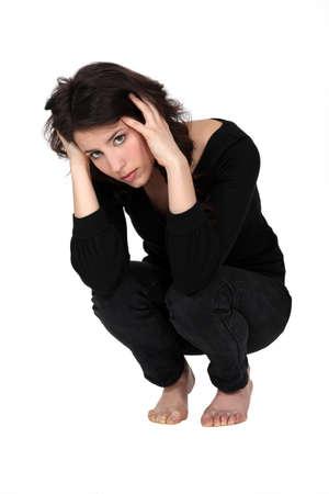 en cuclillas: Una mujer deprimida en cuclillas