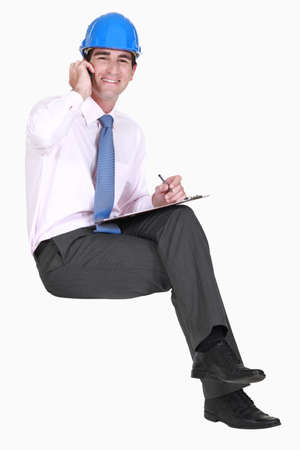 Surveyor sitting on an invisible stool and talking on his mobile phone photo