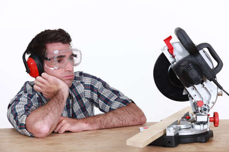miter: Bored man looking at circular saw
