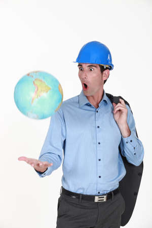 jesting: Engineer tossing a globe Stock Photo