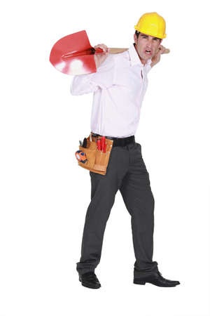 foreman carrying shovel on his back looking furious Stock Photo