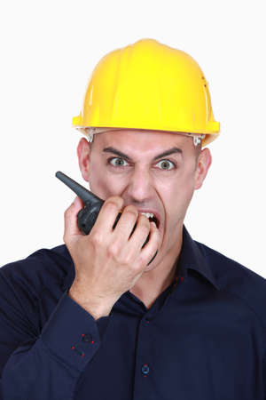 walkie talkie: angry businessman wearing helmet and shouting on a walkie talkie