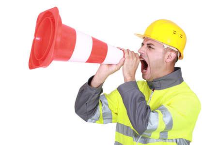 Traffic guard screaming into a pylon