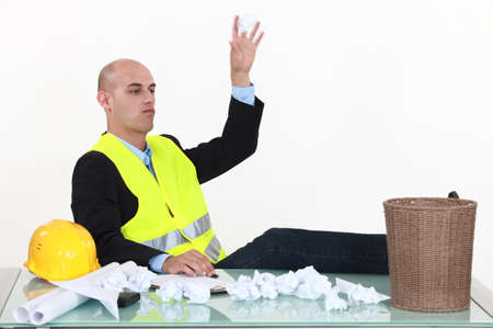 Man throwing papers in trash can photo