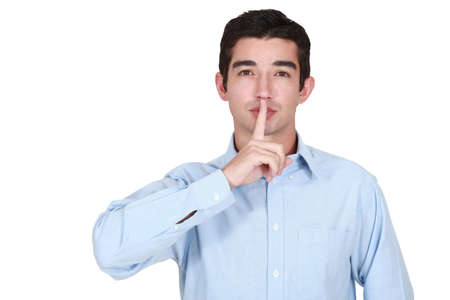 young man holds finger before lips Stock Photo