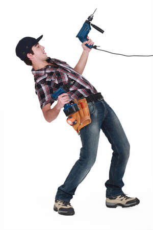 perforate: Young man pulling a drill on white background