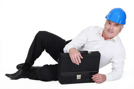 senior architect lying on floor with briefcase photo