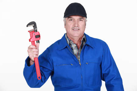 grey haired: Grey haired man holding wrench