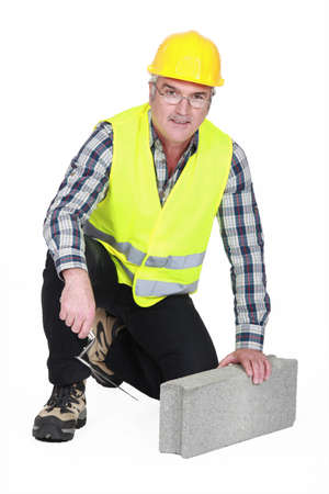 workplace safety: mature bricklayer with concrete block and trowel