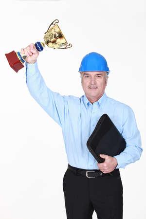 rewarded: Un arquitecto sosteniendo un trofeo.