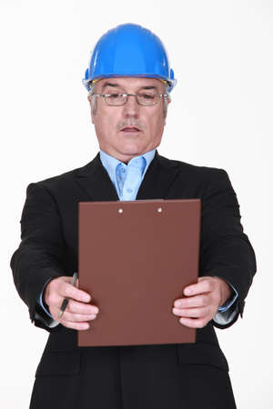 Engineer staring in disbelief at a clipboard photo