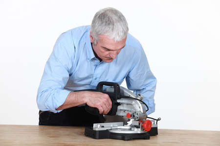 figuring: Man figuring out how to operate his new mitre saw